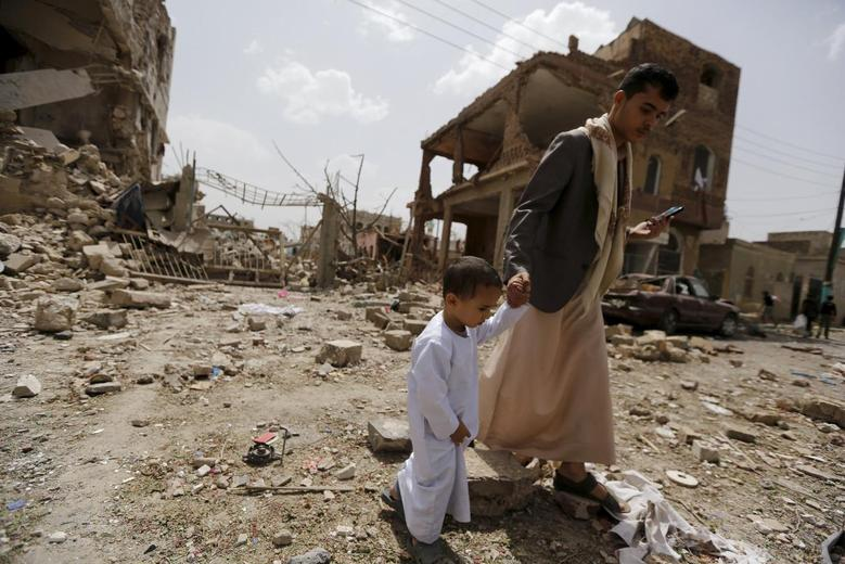 A man and a boy walk at a site hit by a Saudi-led air strike in Yemen's capital Sanaa July 3, 2015. REUTERS/Khaled Abdullah