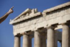 Турист у здания Парфенона в Афинах 9 июля 2015 года. Греция готовит двухлетнюю программу реформ стоимостью 12 миллиардов евро ($13,33 миллиарда) в попытке компенсировать возвращение в рецессию после долгих переговоров с кредиторами, сообщила газета Kathimerini. REUTERS/Christian Hartmann