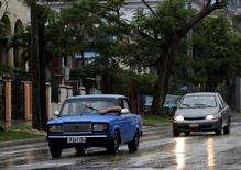 A man tries to adjust the windshield wiper of his Lada while driving in the rain in Havana February 8, 2015. The former Soviet Union began exporting its cheaply built models to Cuba in the 1970s until production began to peter out a decade ago. Very little evidence of Soviet influence remains in Cuba, except the spunky little Russian-made Lada cars, famous for rattling chassis but sturdy engines. With state salaries pegged at barely $20 a month, few Cubans can afford to buy new cars, so the parts business plays a crucial role in keeping the aging models on the road. The U.S. trade embargo prevents parts from being shipped to Cuba. But Cubans visiting Miami can buy them take them back to the island, or have U.S.-based relatives find someone traveling to Havana to take them. Picture taken February 8, 2015. To match Feature USA-MIAMI/CUBA-CARS  REUTERS/Enrique De La Osa (CUBA - Tags: POLITICS TRANSPORT SOCIETY)