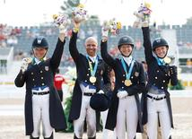 (L-R) Kimberley Herslow , Steffen Peters , Sabine Schut-Kery and Laura Graves of the United States celebrate after winning the gold medal in the Team Dressage during the 2015 Pan Am Games at Caledon Pan Am Equestrian Park. Mandatory Credit: Geoff Burke-USA TODAY Sports