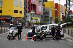 Полицейские у торгового центра в Вильнев-ла-Гаренн. 13 июля 2015 года. Полицейские эвакуировали 18 человек из магазина одежды в торговом центре в пригороде Парижа, который подвергся ограблению, сообщили источники во французской полиции. REUTERS/Hedy Belucif