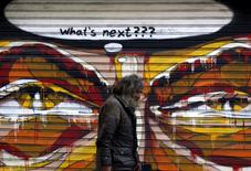 Граффити в Афинах. 14 июля 2015 года. Греции понадобится списание долга намного большее, чем планируют обсудить ее партнеры по еврозоне, в связи с плачевным состоянием ее экономики и банков в последние две недели, говорится в конфиденциальном исследовании Международного валютного фонда, с которым ознакомился Рейтер. REUTERS/Yannis Behrakis