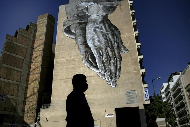 A pedestrian walks through empty streets by a mural in Athens, Greece July 12, 2015.  REUTERS/Yannis Behrakis