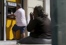 Una persona retira dinero de un cajero automático del banco Piraeus en Atenas, jul 13 2015. Alemania podría evaluar la posibilidad de que Grecia pague su deuda a un plazo mayor, pero sólo si no insiste con una reducción de lo que debe, dijo el miércoles el Ministerio de Finanzas germano.     REUTERS/Christian Hartmann