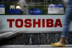 Pedestrians walk past a logo of Toshiba Corp outside an electronics retailer in Tokyo, Japan, June 25, 2015.  REUTERS/Yuya Shino