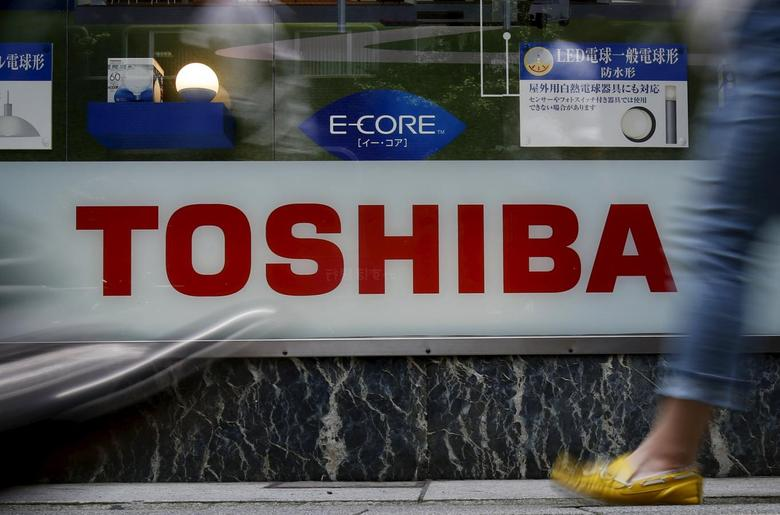 Pedestrians walk past a logo of Toshiba Corp outside an electronics retailer in Tokyo, Japan, June 25, 2015.  REUTERS/Yuya Shino