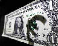 Тень символа евро на банкноте 1 доллар США. Мадрид, 10 марта 2015 года. Курс евро снижается, после того как парламент Греции утвердил экономические реформы, необходимые для получения новых кредитов. REUTERS/Sergio Perez