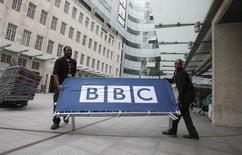Funcionários movendo placa com logo da BBC na entrada da sede da emissora, em Londres.   16/07/2015   REUTERS/Peter Nicholls