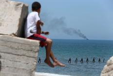 Palestinos observam fumaça em embarcação do Egito na costa norte do Sinai, a partir da fronteira da Faixa de Gaza com o Egito. 16/07/2015 REUTERS/Ibraheem Abu Mustafa