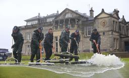 Groundstaff remove water from the 18th green after torrential rain forced play to be suspended during the second round of the British Open golf championship on the Old Course in St. Andrews, Scotland, July 17, 2015.    REUTERS/Eddie Keogh