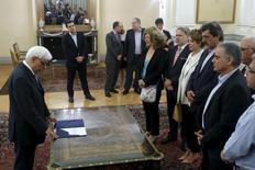 Los nuevos ministros de Grecia fueron investidos el sábado después de que el primer ministro Alexis Tsipras llevase a cabo una remodelación para expulsar a los disidentes de su gabinete y comenzar una nueva fase en las negociaciones por un tercer acuerdo de rescate. En la imagen, el presidente de Grecia, Prokopis Pavlopoulos, preside la ceremonia de investidura de los nuevos cargos del gobierno griego en una fotografía tomada el 18 de julio de 2015 en el palacio presidencial de Atenas. REUTERS/Alkis Konstantinidis