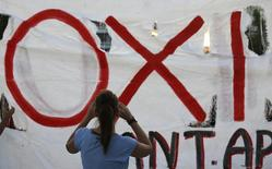 "The word ""No"" in Greek is seen on a banner as anti-austerity protesters gather in front of the Parliament building in Athens, Greece, July 12, 2015. Euro zone leaders told near-bankrupt Greece at an emergency summit on Sunday that it must restore trust by enacting key reforms before they will open talks on a new financial rescue to keep it in the European currency area.    REUTERS/Yannis Behrakis"