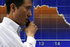 File photo of a man using a mobile phone as he walks in front of a graph showing today's Nikkei share average movements outside a brokerage in Tokyo, June 9, 2015. REUTERS/Issei Kato