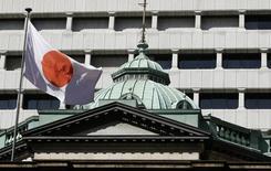 Una bandera japonesa ondea sobre la sede del Banco de Japón, en Tokio, 26 de octubre de 2011. Varios miembros del directorio del Banco de Japón dijeron que el impacto de su estímulo podría estar disipándose, según las minutas de su encuentro de junio, una señal de que no todos comparten el optimismo del gobernador del banco central, Haruhiko Kuroda, sobre la posibilidad de alcanzar la meta inflacionaria de un 2 por ciento. REUTERS/Yuriko Nakao