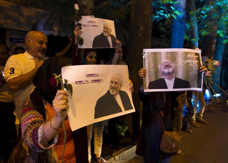 Iranians hold pictures of Iranian Foreign Minister Mohammad Javad Zarif as they celebrate in the street following a nuclear deal with major powers, in Tehran July 14, 2015. REUTERS/TIMA