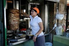 """Una empleada preparando la carne a la brasa conocida como """"Gyros"""" en el centro de Atenas, 20 de julio de 2015. Para los turistas que merodean por las estrechas calles del centro de Atenas, 20 céntimos en el precio del souvlaki - la tradicional brocheta de carne a la brasa - pueden no parecer mucho. Pero para el camarero Stavros Giokas, la subida del IVA que se aplica desde el lunes es una gran preocupación. REUTERS/Yiannis Kourtoglou"""
