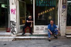 Unos hombres sentados frente a una tienda en Atenas, el 21 de julio de 2015. Grecia espera que las negociaciones con sus acreedores internacionales sobre un paquete de rescate hayan concluido para el 20 de agosto, dijo el martes Olga Gerovasili, portavoz del Gobierno. REUTERS/Yiannis Kourtoglou