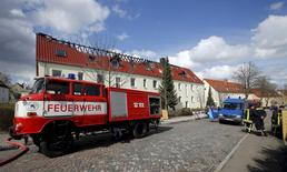 A fire engine is seen in front of a building which was meant to be an asylum shelter, after it was damaged in a fire in Troeglitz April 4, 2015. The blaze was not the first attack on a refugee shelter in Germany but it shocked a nation that has received a surge of refugees in the last few years -- 200,000 in 2014 and a further 85,000 in the first quarter of 2015 alone. A state police spokesman said they were still investigating the fire that gutted the top floor of the three-storey building, but they believe it was started deliberately. Picture taken April 4. REUTERS/Fabrizio Bensch