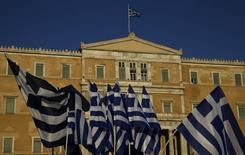 """Imagen de archivo de unas banderas de Grecia flameando frente al Parlamento en Atenas, jul 15 2015. La agencia Standard & Poor's elevó el martes la calificación crediticia de Grecia a """"CCC+"""" desde """"CCC"""" y mejoró su panorama a estable desde negativo, al considerar que los riesgos en los próximos 12 meses para la deuda están equilibrados.      REUTERS/Yannis Behrakis"""