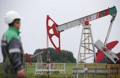 Рабочий у станка-качалки на Бузовьязовском месторождении Башнефти к северу от Уфы 11 июля 2015 года. Цены на нефть снижаются в среду на фоне роста запасов нефти в США за неделю вопреки ожиданиям аналитиков, хотя ослабление доллара и помогло ограничить падение. REUTERS/Sergei Karpukhin