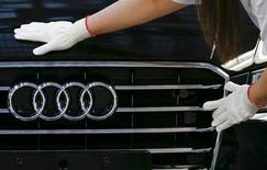 A worker fixes a car emblem as she assembles Audi A8 models at their plant in Neckarsulm near Heilbronn May 21, 2015.   REUTERS/Michael Dalder
