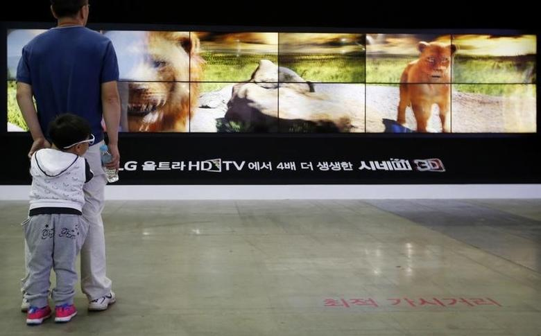 A man and his son look at LG Electronics' 3D TV sets, which are made with LG Display flat screens, during the 2014 Korea Electronics Show in Goyang October 17, 2014.  REUTERS/Kim Hong-Ji