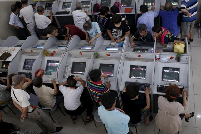 7月23日、中国が株式市場下支えのために打ち出した対策の規模が、官民合わせて5兆元(8052億ドル)相当に上ったことがロイターの分析で分かった。写真はスクリーンを眺める投資家、上海の証券会社で13日撮影(2015年 ロイター/Aly Song)