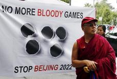 """Тибетский монах на фоне плаката """"Нет еще одним кровавым играм. Останови Пекин-2022"""" на акции протеста в Лозанне 10 июня 2015 года. Группа правозащитников указала Международному олимпийскому комитету на ущемление прав человека в Китае как основание отказать в праве принять зимнюю Олимпиаду-2022 Пекину, единственным конкурентом которого выступает Алма-Ата. REUTERS/Ruben Sprich"""