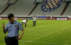 Сотрудники полиции на стадионе в Сплите после игры Хорватии и Италии 12 июня 2015 года. УЕФА лишил сборную Хорватии очка в рамках отборочного турнира чемпионата Европы 2016 года и наказал команду двумя матчами без зрителей за свастику, нанесенную на газон стадиона в городе Сплит. REUTERS/Antonio Bronic