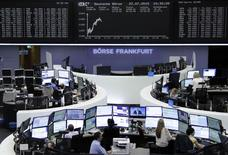 Traders are pictured at their desks in front of the DAX board at the Frankfurt stock exchange July 22, 2015.   REUTERS/Remote/Staff