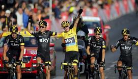 Team Sky rider Chris Froome of Britain (C), the race leader's yellow jersey, celebrates his overall victory with team-mates after the 109.5-km (68 miles) final 21st stage of the 102nd Tour de France cycling race from Sevres to Paris Champs-Elysees, France, July 26, 2015. REUTERS/Stephane Mahe