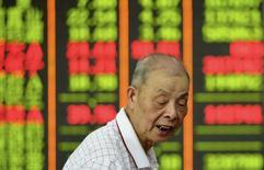 La Bolsa de China se dejó más de un ocho por ciento, su mayor pérdida diaria en más de ocho años, agotándose la recuperación propiciada por el Gobierno en medio de una toma de ganancias, las preocupaciones sobre la salud de su economía y los temores a que termine la postura de Pekín hacia políticas monetarias más laxas En la imagen, un inversor pasa junto a un panel electrónico en Hangzhou, provincia de Zhejiang, el 27 de julio de 2015. REUTERS/China Daily