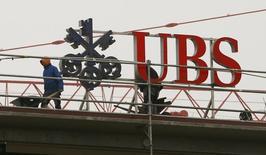 El banco suizo UBS <UBSG.VX> dijo el lunes que su beneficio neto aumentó un 53 por ciento en el segundo trimestre frente al mismo período del año previo a 1.200 millones de francos suizos (1.250 millones de dólares), comunicando sus resultados un día antes que lo fijado después de que un semanario suizo publicara una información sobre las cifras el domingo. En la imagen, unos trabajadores en la sede de UBS en Zúrich, el 13 de febrero de 2015. REUTERS/Arnd Wiegmann