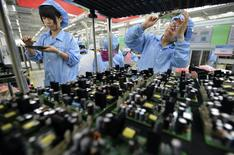 Empleados trabajando en una línea de producción de paneles electrónicos en una fábrica de FiberHome Technologies Group, en Wuhan, Provincia de Hubei, China, 27 de julio de 2015. Las ganancias industriales chinas, que aumentaron en una tasa interanual en abril y mayo, cayeron en junio, aumentando las presiones sobre una economía que lucha por recuperar el impulso. REUTERS/China Daily