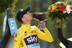 Team Sky rider Chris Froome of Britain, the race leader's yellow jersey, celebrates his overall victory on the podium after the final 21st stage of the 102nd Tour de France cycling race from Sevres to Paris Champs-Elysees, France, July 26, 2015. REUTERS/Benoit Tessier