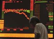 Un inversor pasa frente a un panel con información bursátil en Fuyang, China, jul 27 2015. China incrementará las compras de acciones, dijo el lunes el regulador de valores del país, según un informe de la cadena de televisión financiera CNBC. REUTERS/Stringer
