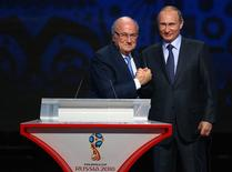 FIFA's President Sepp Blatter shakes hands with Russia's President Vladimir Putin (R) during the preliminary draw for the 2018 FIFA World Cup at Konstantin Palace in St. Petersburg, Russia July 25, 2015. REUTERS/Stringer