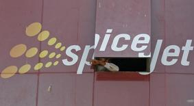 A man looks out through a window with an advertisement of SpiceJet Airline, on a commercial building in the western Indian city of Ahmedabad February 14, 2014. REUTERS/Amit Dave/Files