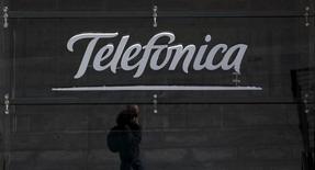 Un hombre hablando por celular se refleja en una tienda de Telefónica, en Madrid, 28 de abril de 2015.  La firma brasileña Telefónica Brasil SA reportó el miércoles una caída de un 56,4 por ciento interanual en su ganancia neta en el segundo trimestre, a 932,9 millones de reales (259,14 millones de dólares), incumpliendo la previsión de 1.018 millones de reales arrojada en un sondeo de Reuters. REUTERS/Sergio Perez
