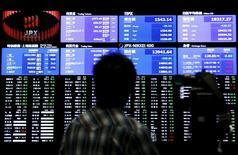 Una persona filma un tablero electrónico que muestra el índice Nikkei y otros índices relacionados, en la Bolsa de Tokio, Japón, 9 de julio de 2015. Las bolsas de Asia subían levemente el jueves y el dólar consolidaba unas ganancias recientes después de que la Reserva Federal de Estados Unidos ofreció una visión relativamente optimista de la economía, pero unas ventas intensificadas de las materias primas limitaban las ganancias. REUTERS/Yuya Shino