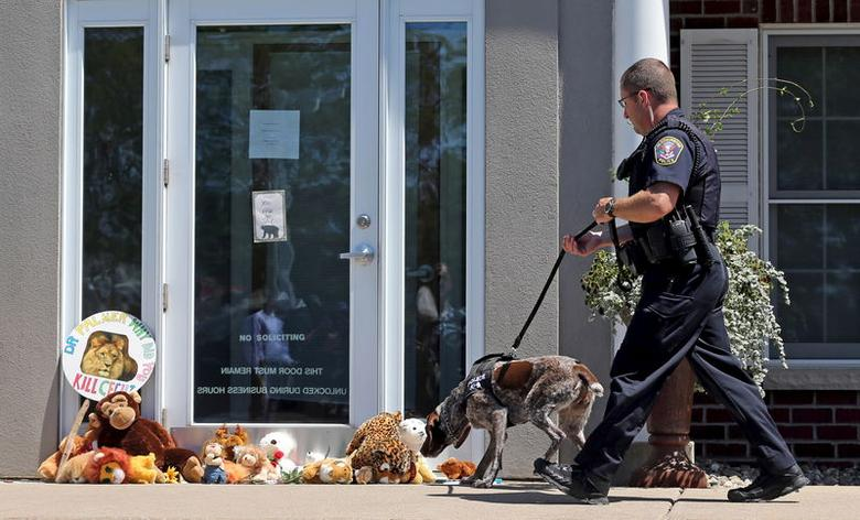 A K-9 Unit Bloomington Police dog sniffs at stuffed animals blocking the doorway of River Bluff Dental clinic in protest against the killing of a famous lion in Zimbabwe, in Bloomington, Minnesota July 29, 2015. A Zimbabwean court on Wednesday charged a professional local hunter Theo Bronkhorst with failing to prevent an American from unlawfully killing 'Cecil', the southern African country's best-known lion. The American, Walter James Palmer, a Minnesota dentist who paid $50,000 to kill the lion, has left Zimbabwe. He says he did kill the animal but believed the hunt was legal and that the necessary permits had been issued. REUTERS/Eric Miller
