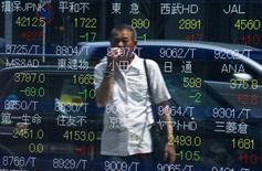 Un hombre mira los precios de las acciones, en un tablero que muestra los índices de mercado en Tokio, 28 de julio de 2015. El índice Nikkei de Japón subió el viernes en una sesión volátil luego de que los inversores se animaron por unas sólidas ganancias corporativas japonesas. REUTERS/Thomas Peter