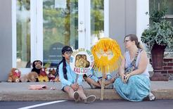 Hayley Hoppe (R) sits with her daughters Piper, 10, (L) and Paisley, 8, (C), in front of the doorway of River Bluff Dental clinic in protest against the killing of a famous lion in Zimbabwe, in Bloomington, Minnesota July 29, 2015. REUTERS/Eric Miller