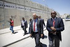 Head of the Palestinian Football Association Jibril Rajoub (2nd R) walks with anti-apartheid activist Tokyo Sexwale (R) past Israel's controversial barrier as they arrive for a news conference in the West Bank town of Al-Ram, near Jerusalem, May 7, 2015. REUTERS/Mohamad Torokman