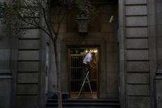 Un trabajador limpia la entrada de un edificio en el centro de Madrid, 29 de julio de 2015. El desempleo registrado en España cayó por sexto mes consecutivo en julio con una reducción mensual de 74.028 personas (1,8 por ciento) que buscaban empleo, una cifra que en términos desestacionalizados arrojó un descenso de 44.286 personas. REUTERS/Susana Vera
