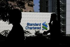 People walk past the main branch of Standard Chartered in Hong Kong in this January 8, 2015 file photo.  REUTERS/Bobby Yip/Files