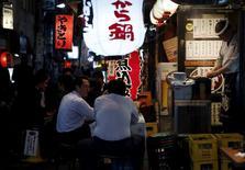 Personas se sientan en bancos afuera de un restaurant con estilo de pub japonés, en un distrito financiero en Tokio, Japón, 30 de abril de 2015. La actividad del sector de servicios de Japón se expandió en julio a un ritmo levemente más lento que el del mes previo, mostró el miércoles un sondeo, lo que sugiere un repunte moderado en la economía tras una esperada contracción en el segundo trimestre. REUTERS/Yuya Shino