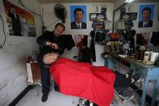 Un peluquero afeita a un cliente junto a un afiche del presidente chino Xi Jinping, en una peluquería en Yongjia, China, 29 de enero de 2015. La actividad en el sector de servicios de China se expandió en julio a su ritmo más veloz en 11 meses, mostró el miércoles un sondeo privado, lo que compensa parte de la presión bajista sobre la segunda mayor economía del mundo por la debilidad de la actividad manufacturera. REUTERS/William Hong