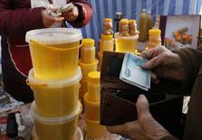 Женщина покупает мед на продуктовой ярмарке в Красноярске. 14 января 2015 года. Индекс потребительских цен в РФ с 28 июля по 3 августа продемонстрировал нулевой рост, как и неделей ранее, сообщил Росстат. REUTERS/Ilya Naymushin