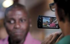 Former U.S. Olympic athlete Carl Lewis is seen through the viewfinder of a video camera as he  attends a media conference before the North, Central America and Caribbean Senior Championships inauguration at the National stadium in San Jose, Costa Rica August 6, 2015. REUTERS/Juan Carlos Ulate